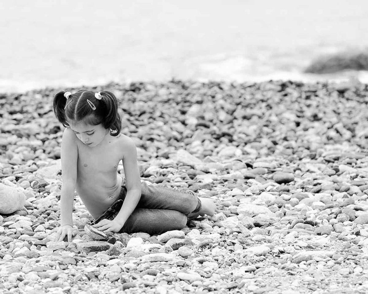 bambina gioca con sassi