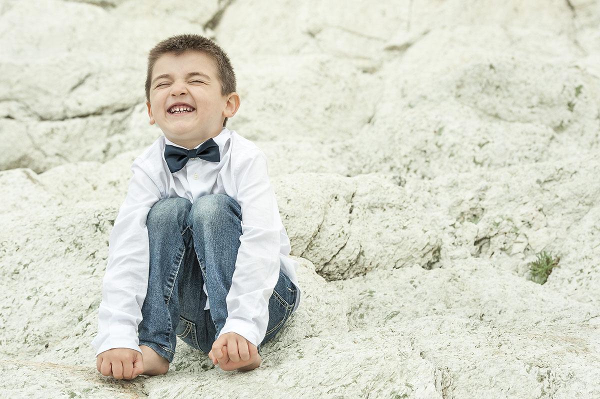 bambino che ride seduto su scoglio