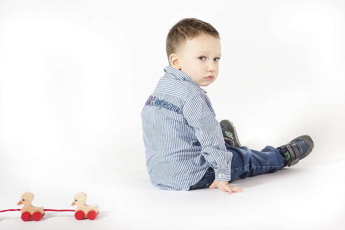 bambino seduto con paperelle